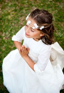 28917321-Cute-little-girl-praying-on-the-background-of-nature-Stock-Photo
